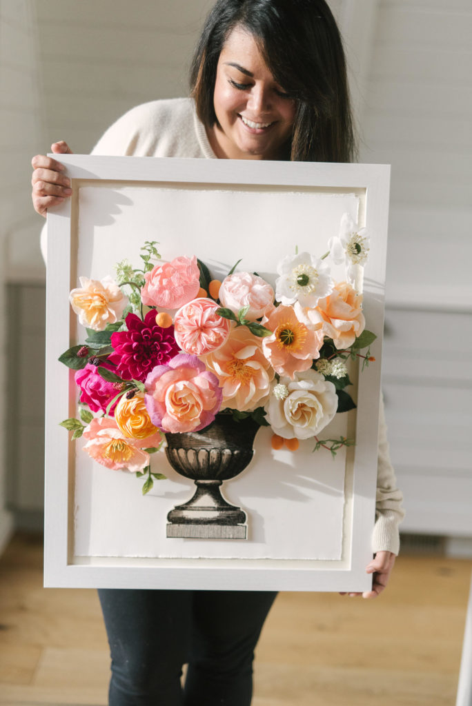 Margie Keates of The Lovely Avenue  studio holds up a paper flower still life.