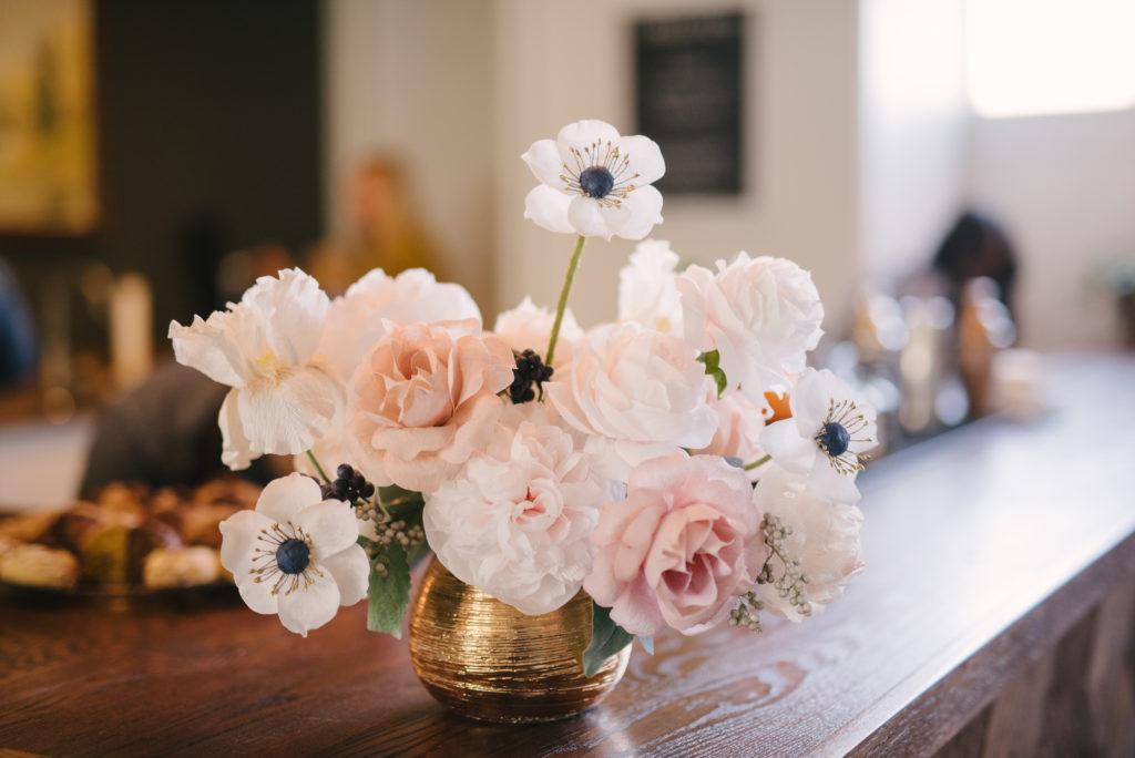 A vase with a paper floral bouquet.
