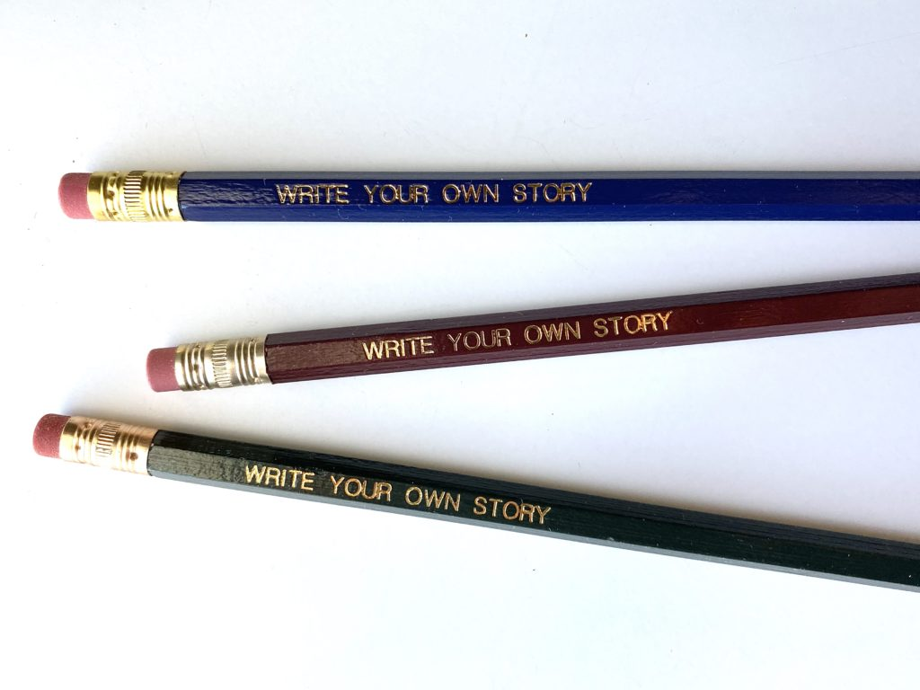 """three pencils with """"write your own story"""" printed on them in gold foil"""