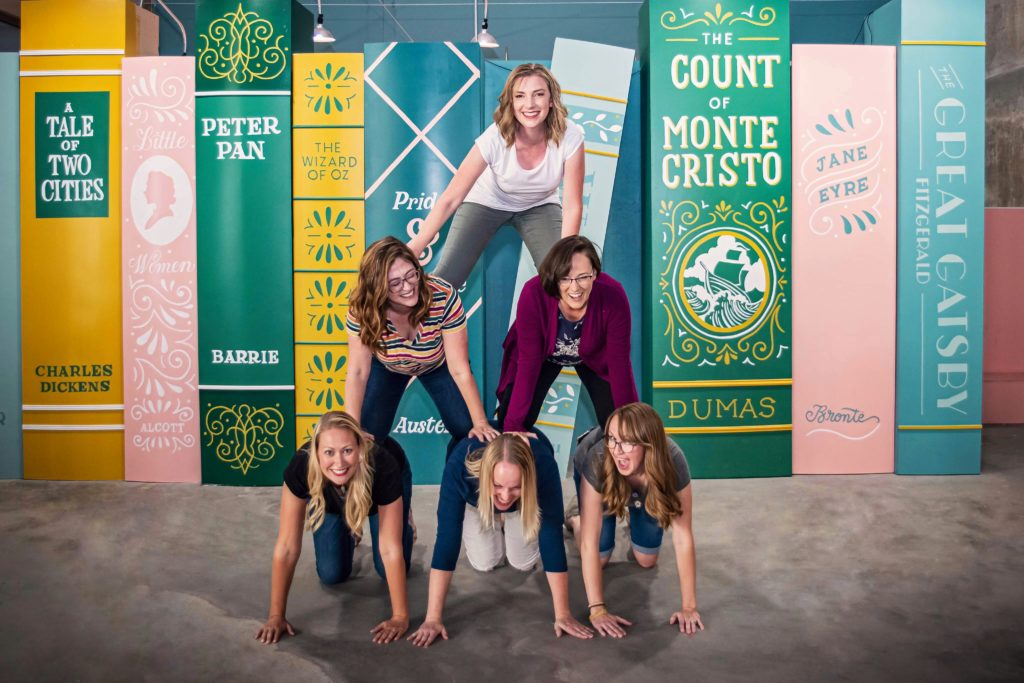 Human pyramid in front of a book mural