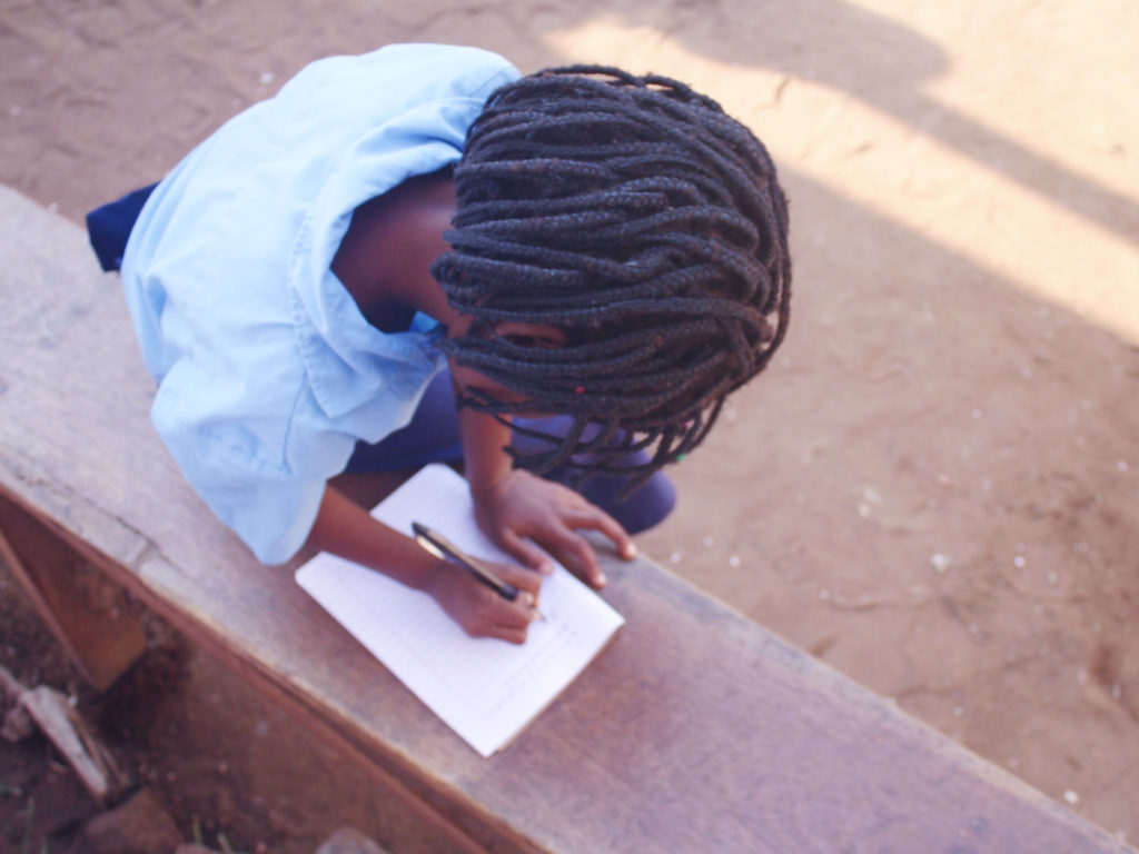 Mozambican girl writing in notebook