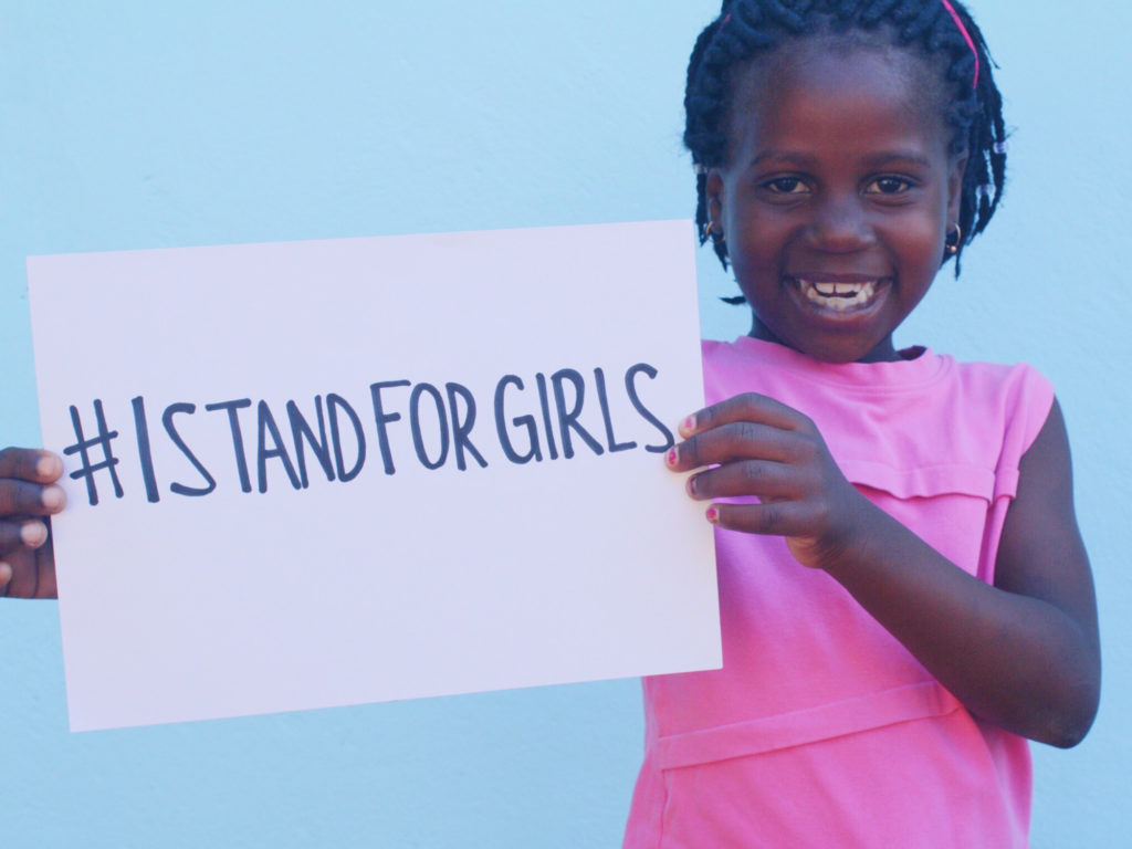 young Mozambican girl holding I Stand For Girls poster